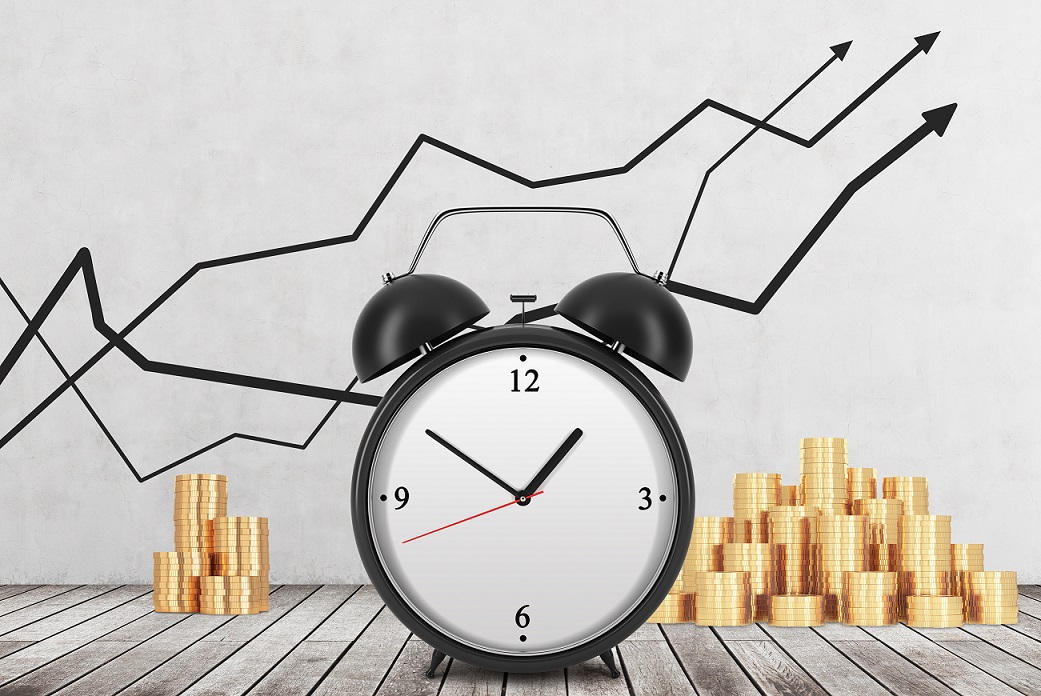 An Alarm clock is on the foreground and golden coins are on the background. Financial line graphs are drawn on the concrete wall. Wooden floor. The concept of time is money. 3D rendering.