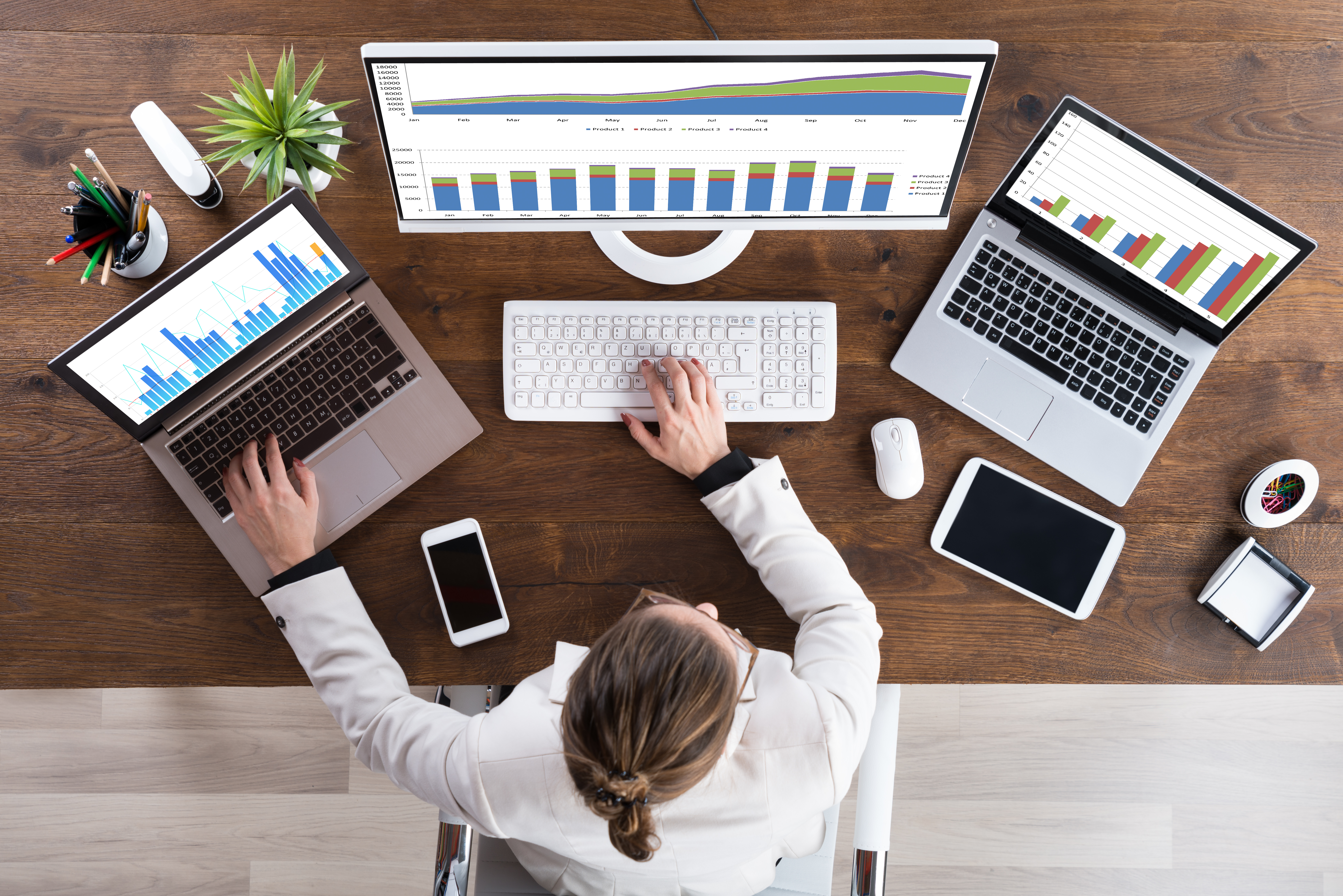High Angle View Of Young Businesswoman Working With Graphs On Computer